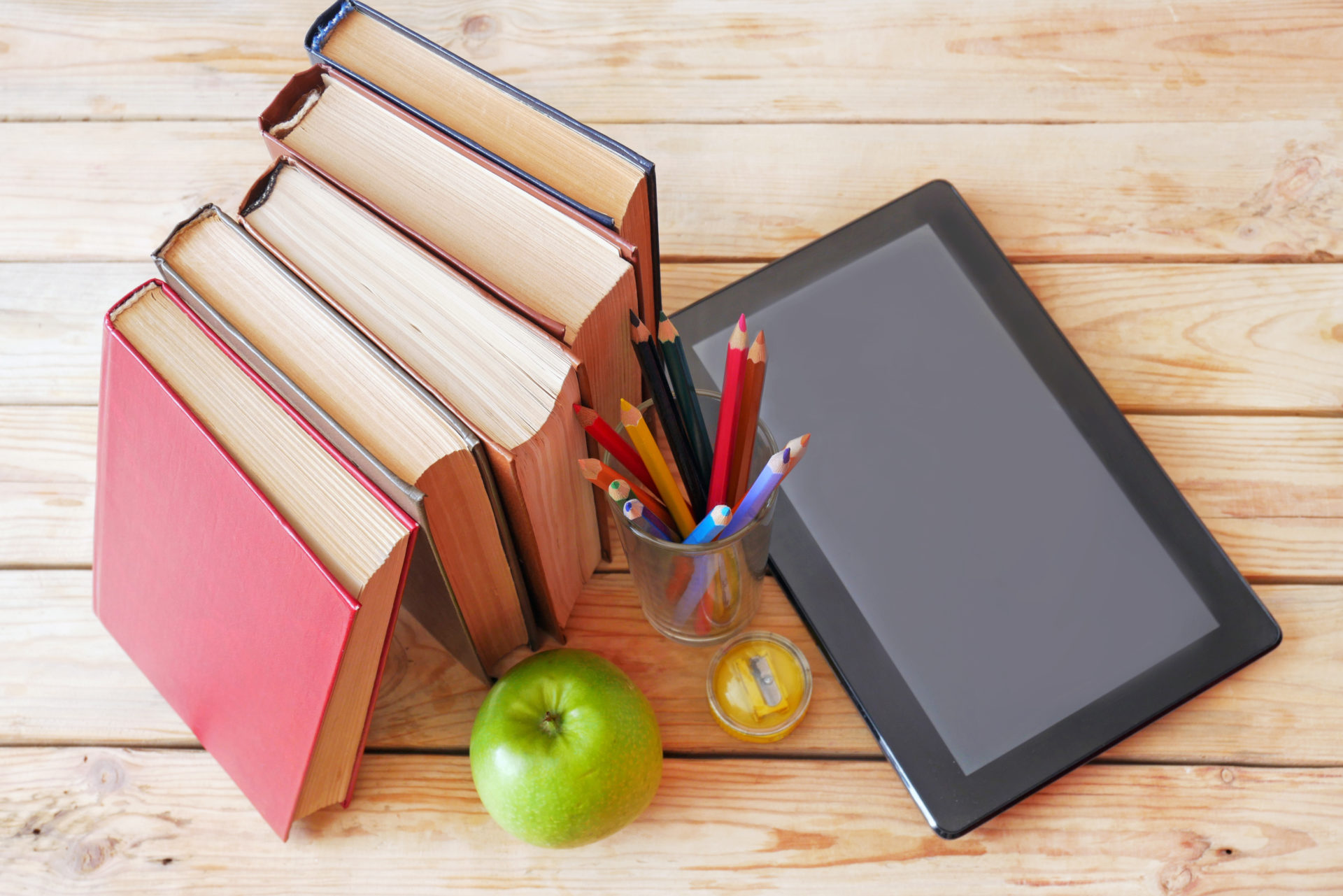 laptop, apple and many books on wooden background, e-learning concept